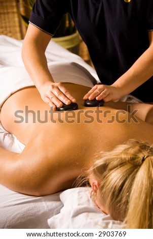 woman at a day spa getting a lastone massage - stock photo