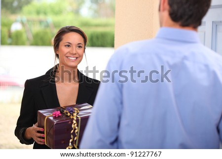 Woman at a front door with a gift - stock photo