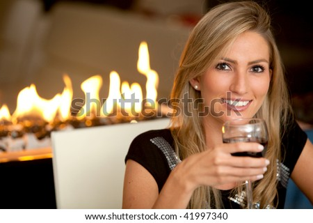 Woman at a romantic dinner with a glass of wine - stock photo