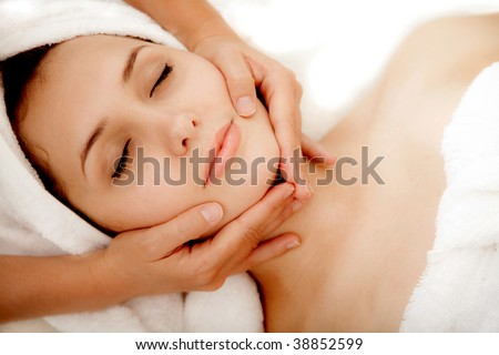 Woman at a spa getting a massage in her face - stock photo