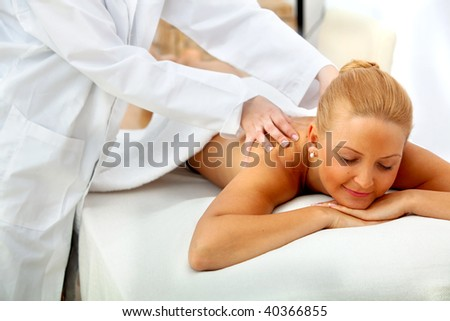 Woman at a spa having a massage on her back - stock photo