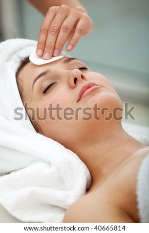 Woman at a spa having a massage on her face - stock photo