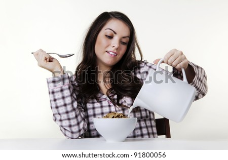 woman at a table in pajamas about to eat cereal - stock photo