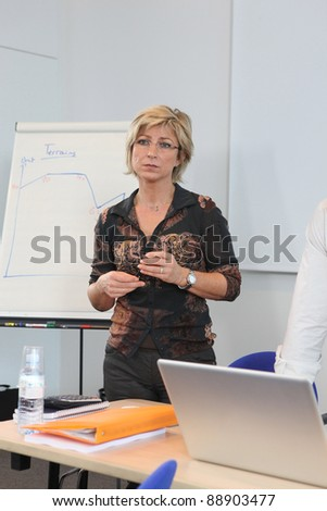 Woman at a whiteboard in a presentation - stock photo