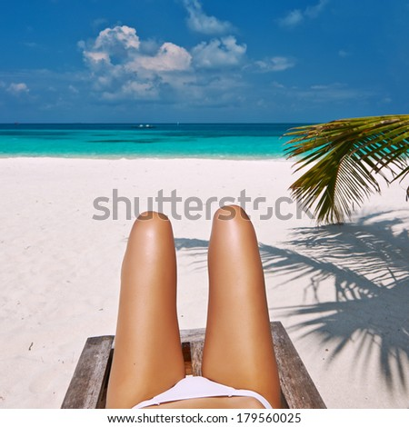 Woman at beautiful beach lying on chaise lounge - stock photo
