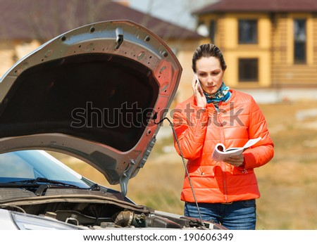 woman at broken car with open hood call  service for help - stock photo