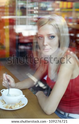 Woman at cafe looking in the window . Eating soup.