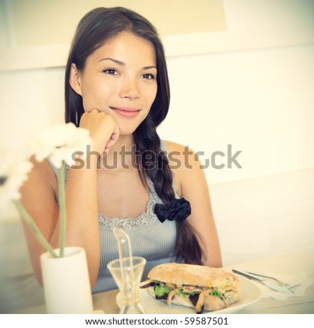 Woman at cafe thinking happy and smiling. Young beautiful Caucasian / Asian female model. Image is cross-processed giving retro style. - stock photo