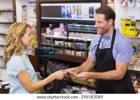 Woman at cash register paying with credit card in supermarket - stock photo