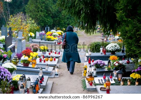 Woman at cemetery alley, All Saints Day, Wroclaw, Poland - stock photo