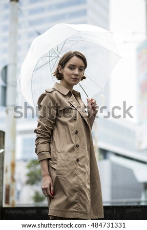 Woman at coat on stairs with umbrella