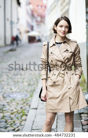 Woman at coat with handbag smile stealthily
