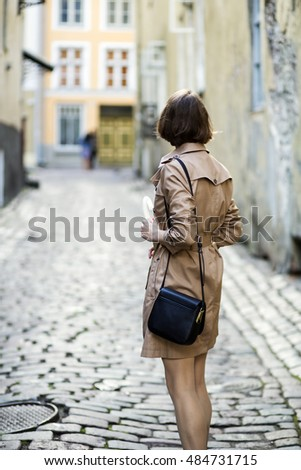 Woman at coat with handbag turned back