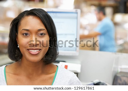 Woman At Computer Terminal In Distribution Warehouse - stock photo