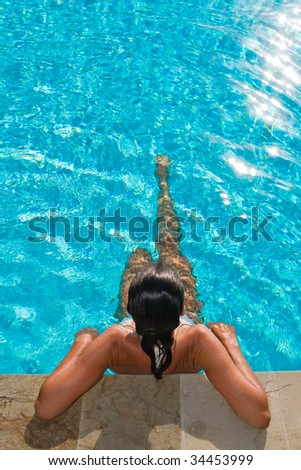 woman at edge of sparkling swimming pool relaxing and sunbathing - stock photo