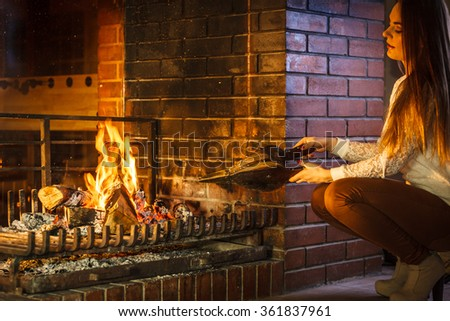 Woman at fireplace making fire with bellows. Young girl heating warming up and relaxing. Winter at home. - stock photo