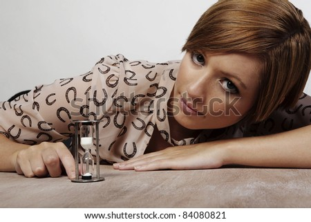 woman at her desk looking at time go by - stock photo