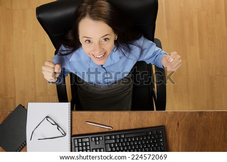 woman at her desk looking up very happy and excited, taken from a birds eye view - stock photo