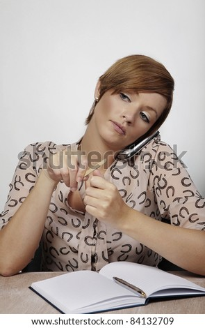 woman at her desk talking on her mobile and doing her nails