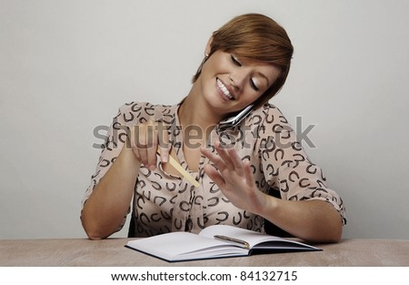 woman at her desk talking on her mobile and doing her nails - stock photo