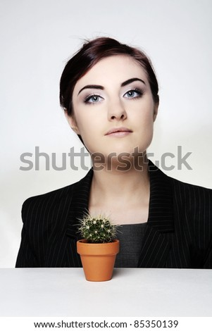 woman at her desk with a small cactus plant in a pot and thinking how things can get prickly around here - stock photo