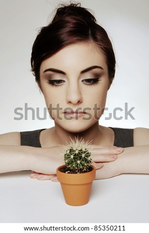 woman at her desk with a small cactus plant in a pot and thinking how things can get prickly around here