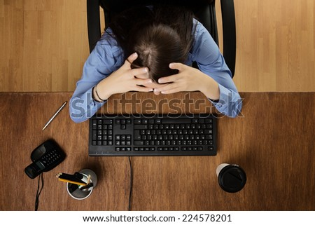 woman at her desk with her head in her hands feeling the stress taken from a birds eye view - stock photo
