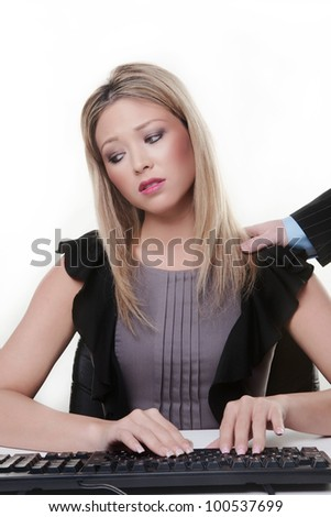 woman at her desk working with a mans hand coming in from the side placed on her left shoulder she not looking to happy about her situation
