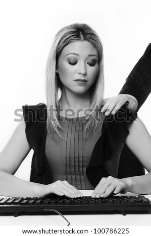 woman at her desk working with a mans hand coming in from the side placed on her left shoulder she not looking to happy about her situation - stock photo