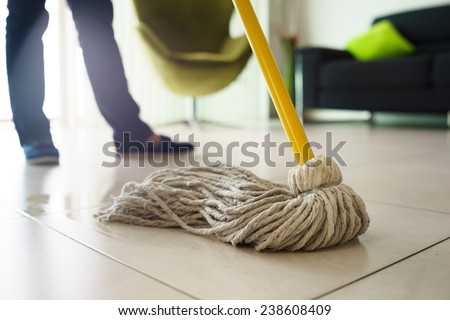 Woman at home, doing chores and housekeeping, wiping floor with water in living room. Focus on floor and mop  - stock photo