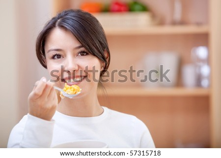 Woman at home eating cereals for breakfast