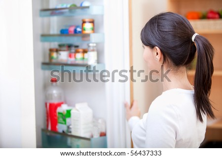 Woman at home looking inside the fridge - stock photo