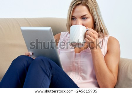 Woman at home relaxing on sofa couch reading email on the tablet computer wifi connection - stock photo