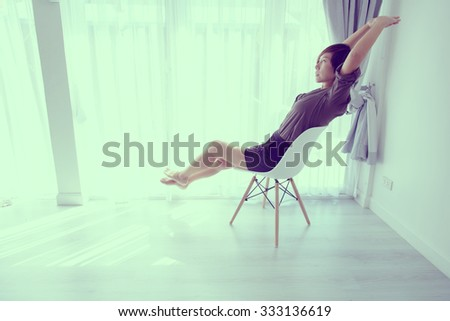 woman at home sitting on modern chair in front of window relaxing in her living room room. Vintage tone.