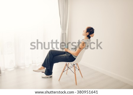 woman at home sitting on modern chair in front of window relaxing in her living room room. Vintage tone. - stock photo