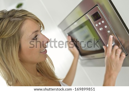 Woman at home using microwave oven - stock photo