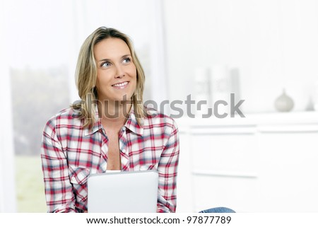 woman at home with tablet looking at someone - stock photo