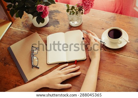 woman at home writing and working with diary. Flowers, notebook, glasses and coffee at wooden table. - stock photo