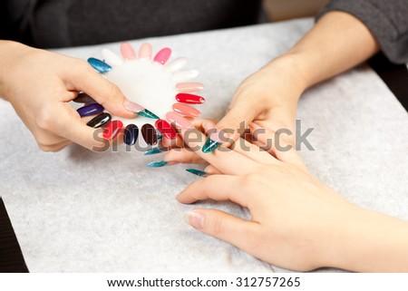 Woman at nail studio chosing color of nail polish - stock photo
