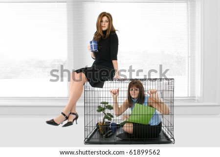 Woman at office in cage looking stressed while woman takes coffee break on top of cage. - stock photo