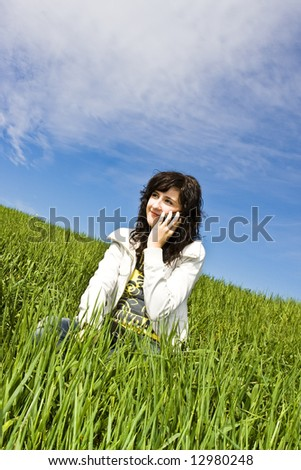 Woman at phone in meadow. - stock photo