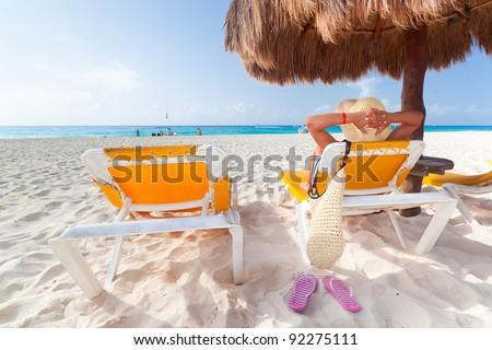 Woman at relaxation under parasol at Caribbean Sea - stock photo