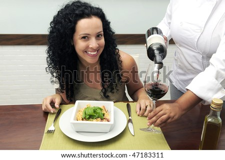 woman at restaurant, chef pouring wine into wineglass - stock photo