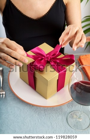 woman at restaurant opening a golden gift package - stock photo