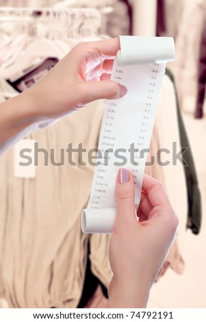 woman at shop or dry-cleaning office holds in her hands roll of paper with printed receipt - stock photo