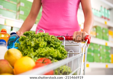 Woman at supermarket pushing a shopping cart filled with fresh fruit and vegetables. - stock photo