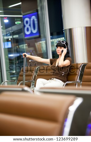 Woman at the airport calling on mobile phone