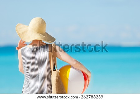 woman at the beach back view holding beach ball and bag - stock photo