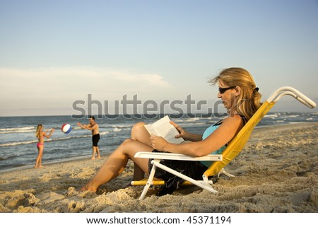 Woman at the beach reads a book while her family plays in the background by the ocean. - stock photo