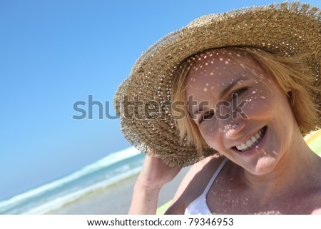 Woman at the beach wearing straw hat